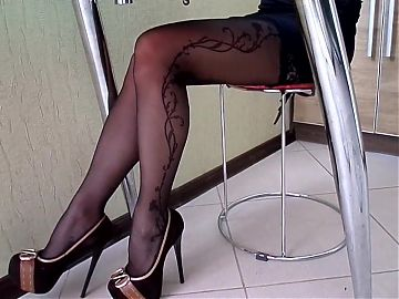 My legs in nylon stockings under the table